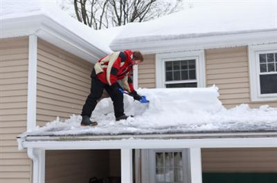 Man shoveling snow off roof.